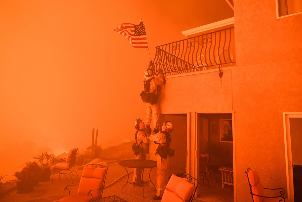 firefighters climbing up to an american flag in a home, in orange
