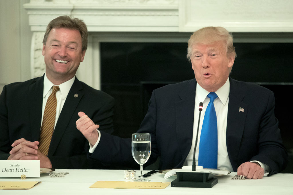 Dean Heller and Donald Trump at a table, both in dark suits