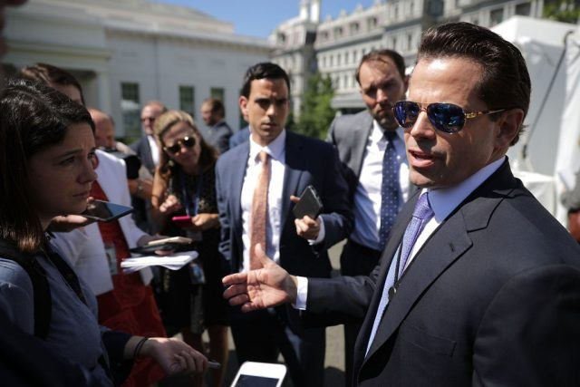 Anthony Scaramucci in sunglasses and a suit addresses members of the media