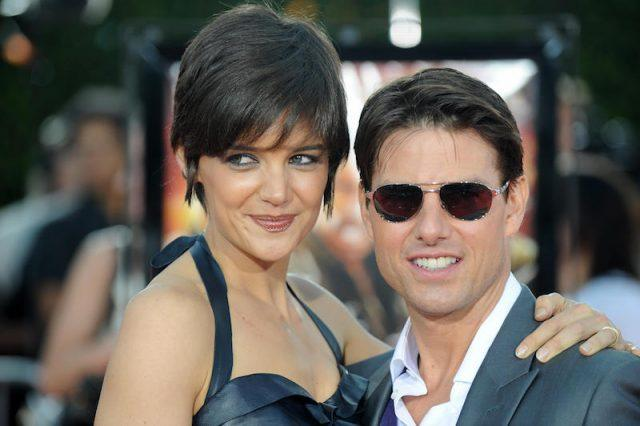 Katie Holmes and Tom Cruise pose for photos on a red carpet.