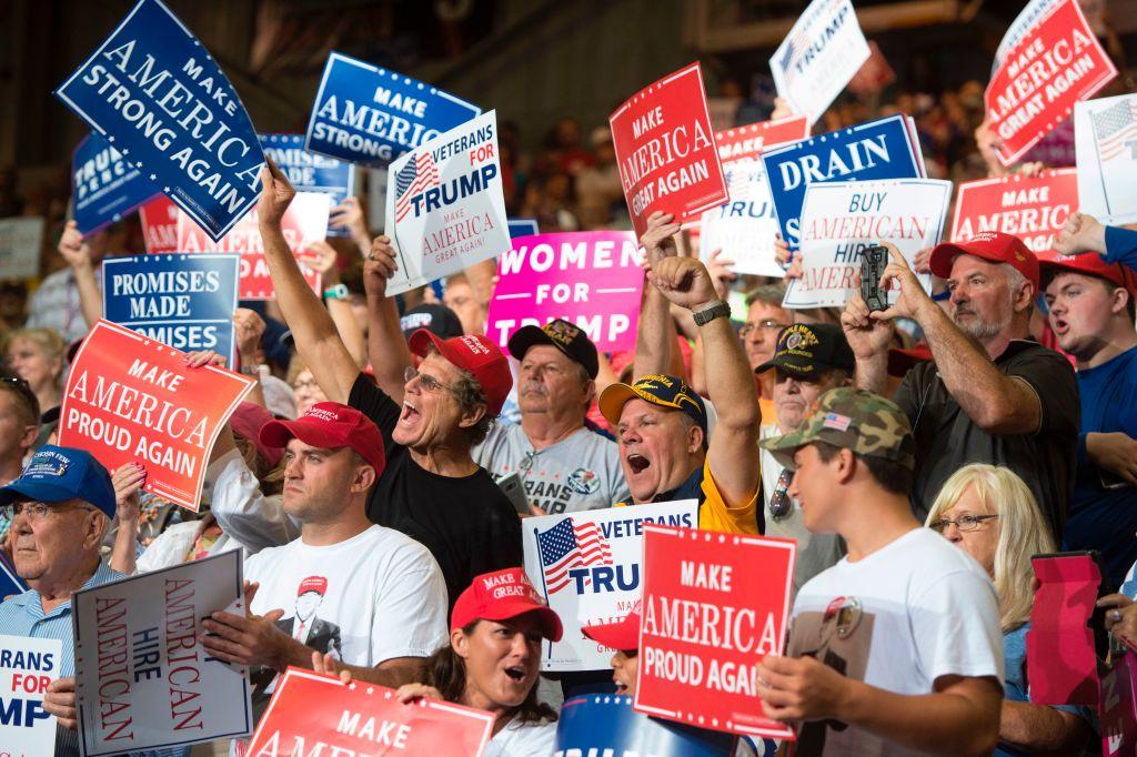 a crowd of Trump fans waving Trump signs