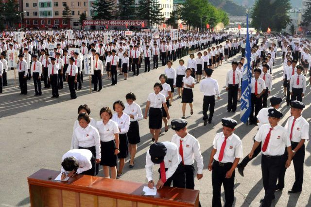 North Korea students in white and red ties lining up to sign petitions.