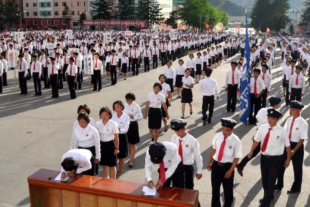 north korea students in white and red ties lining up to sign petitions