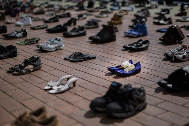 Hundreds of empty shoes on a brick path way representing those lost to suicide.
