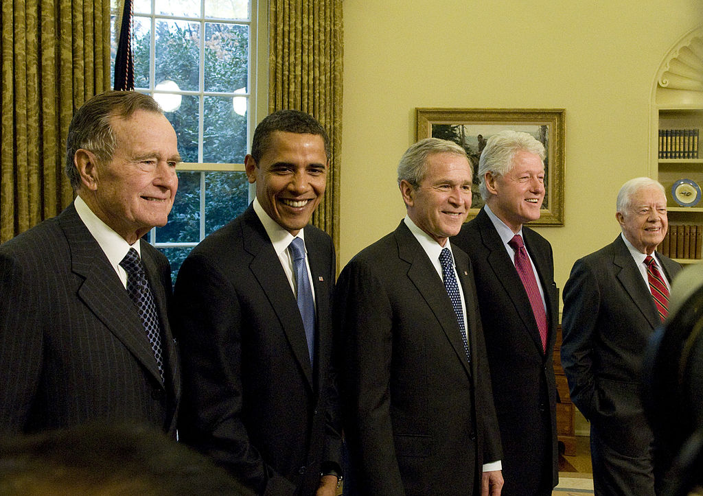 former presidents Bush, Obama, Bush, Carter, and Clinton in a row, all in dark suits