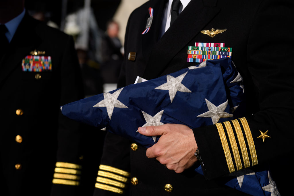 a hand in a blue military uniform with yellow stripes holding a folded American flag, stars out