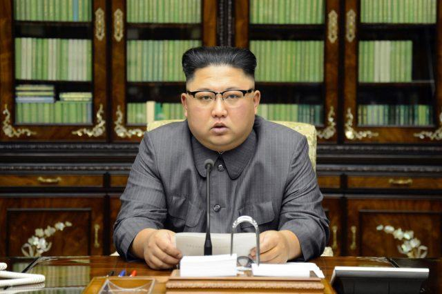 Kim Jong Un giving a statement at a desk with books behind him.