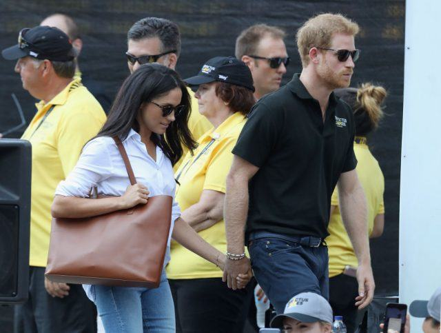 Meghan Markle and Prince Harry holding hands and walking together.