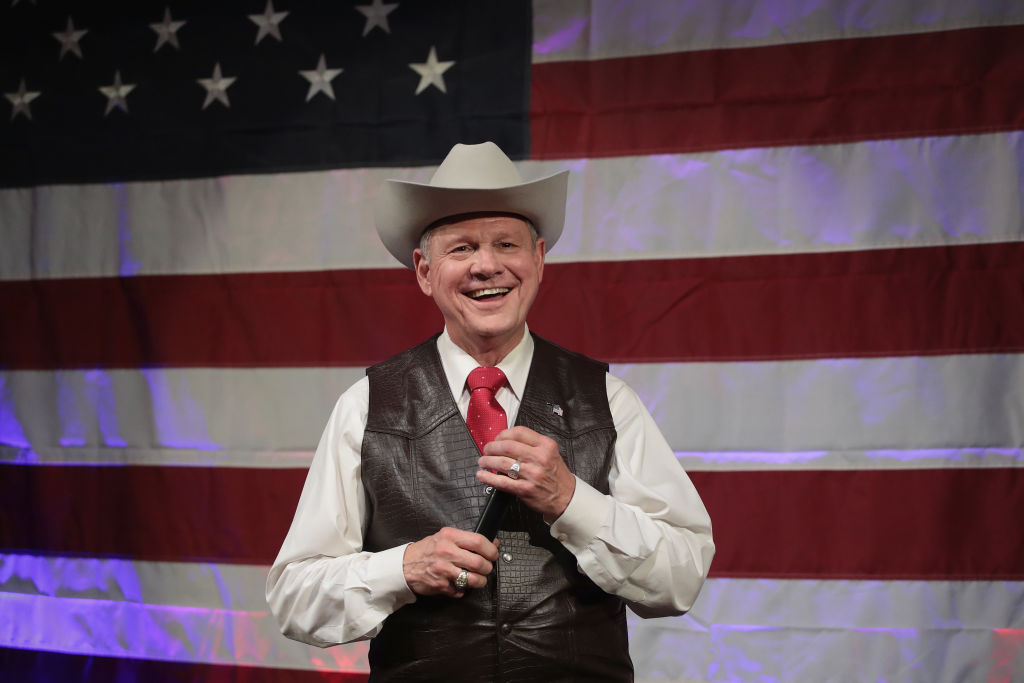Roy Moore wears a leather vest and a cowboy hat, stands against an American flag