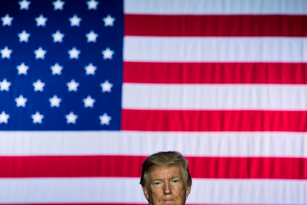 donald trump's head in front of a flag