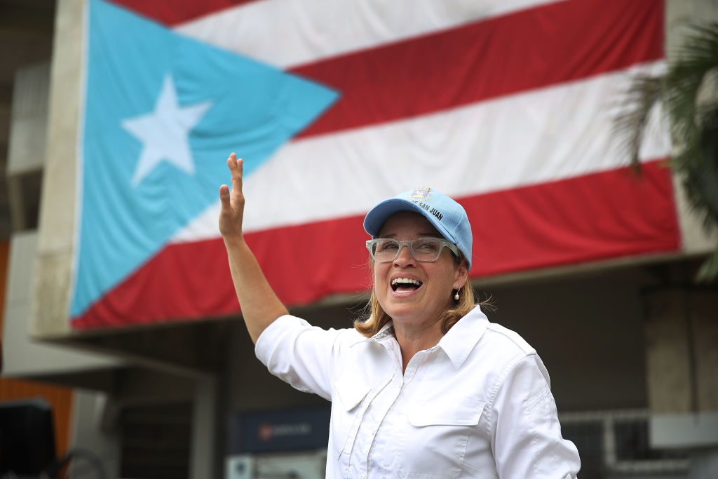 San Juan mayor Carmen Yulin Cruz waves in a white shirt against the Puerto Rico flag
