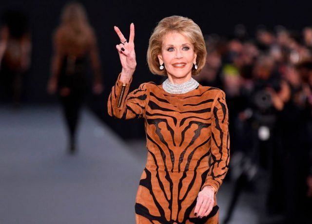 Jane Fonda gestures with a peace sign at a fashion show.