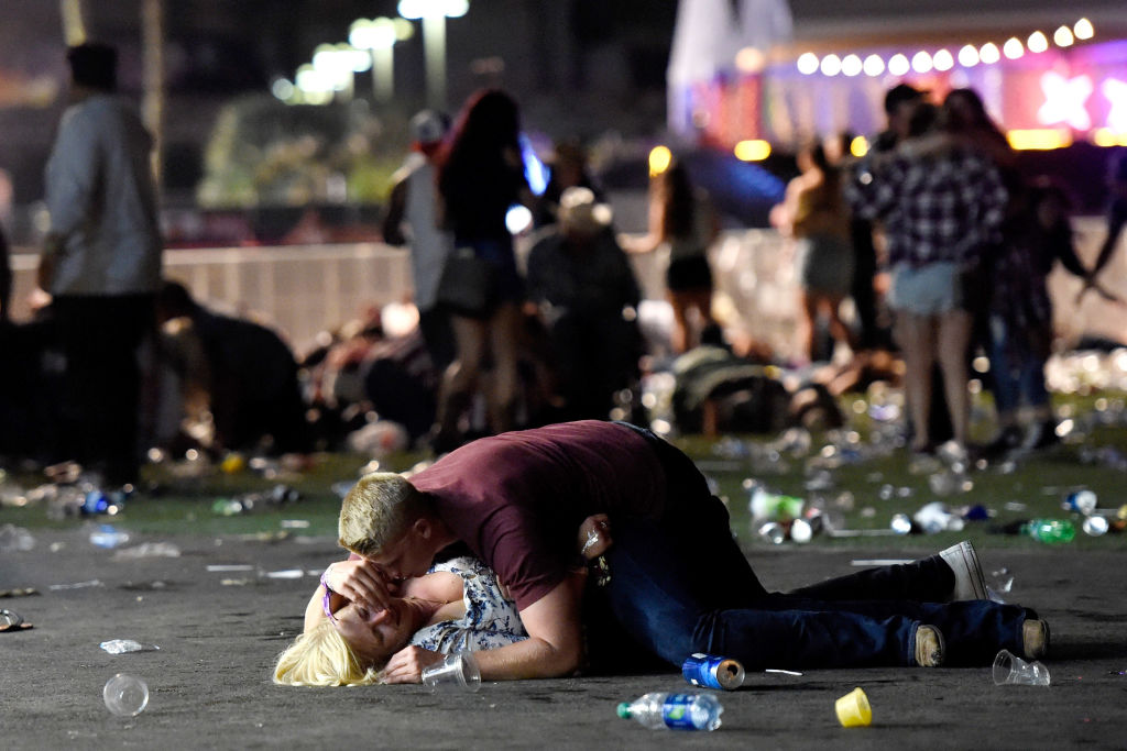 a couple on the ground after Las Vegas shooting surrounded by people.
