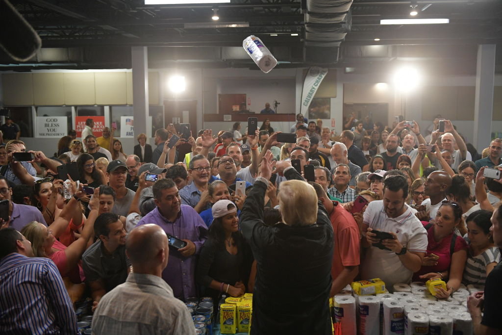 Donald Trump tossing a roll of paper towels into a crowd of people