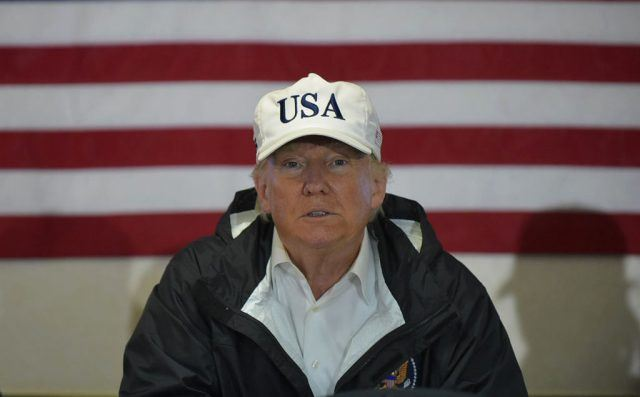 donald trump wearing a USA hat and a windbreaker against an american flag