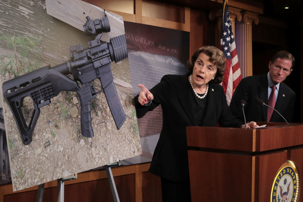 Sen Diane Feinstein in a dark suit points to a photo of a rifle with a bump stock