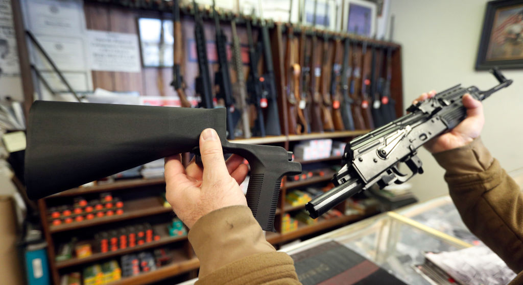 a man holds a bump stock rifle in front of a gun display