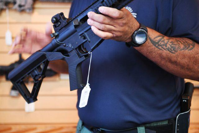 A salesman in a blue shirt shows off a bump stock on a rifle.