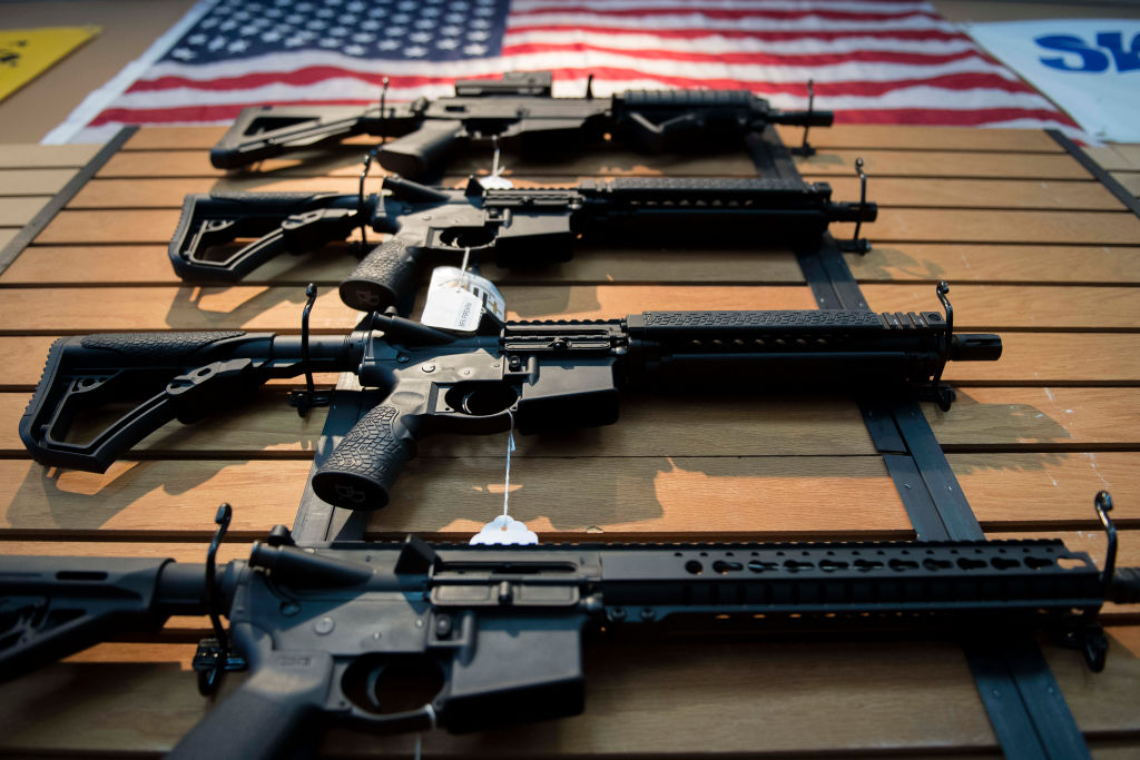 a display of assault rifles on a wood wall beneath an American flag