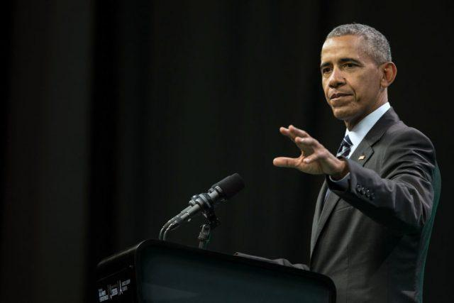 Barack Obama in a dark suit against a black background.