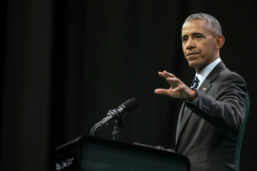 Barack Obama in a dark suit against a black background