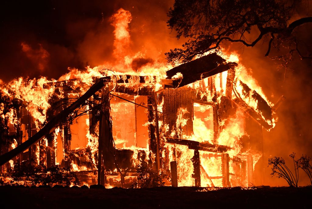 the frame of a house engulfed in flames