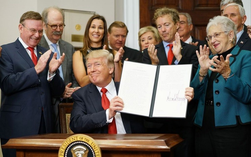 US President Donald Trump shows an executive order which he just signed on health insurance on October 12, 2017 in the Roosevelt Room of the White House in Washington, DC.
