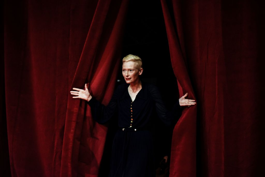 Tilda Swinton pulls back a red curtain