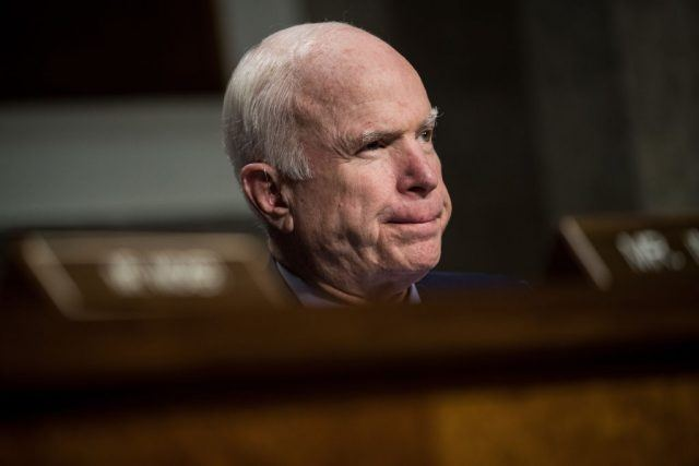 John McCain sitting in front of a wooden bench or table.