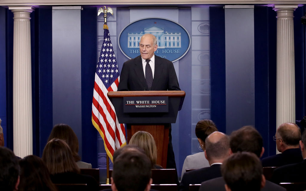 John Kelly talks to the white house press pool in a dark suit