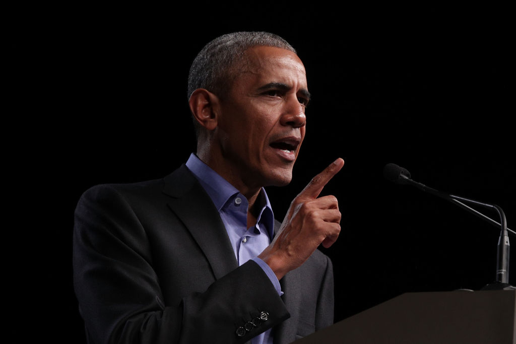 Barack Obama speaking in a dark suit into a microphone.