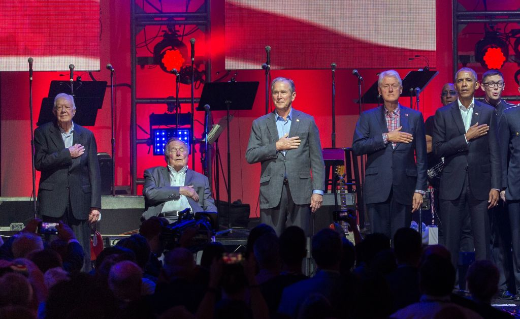 five former presidents with their hands on their hearts, with red, white and blue background