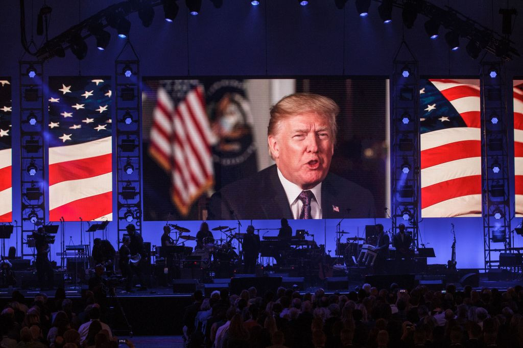 a television screen with Trump speaking backed by an American flag at the hurricane relief concert