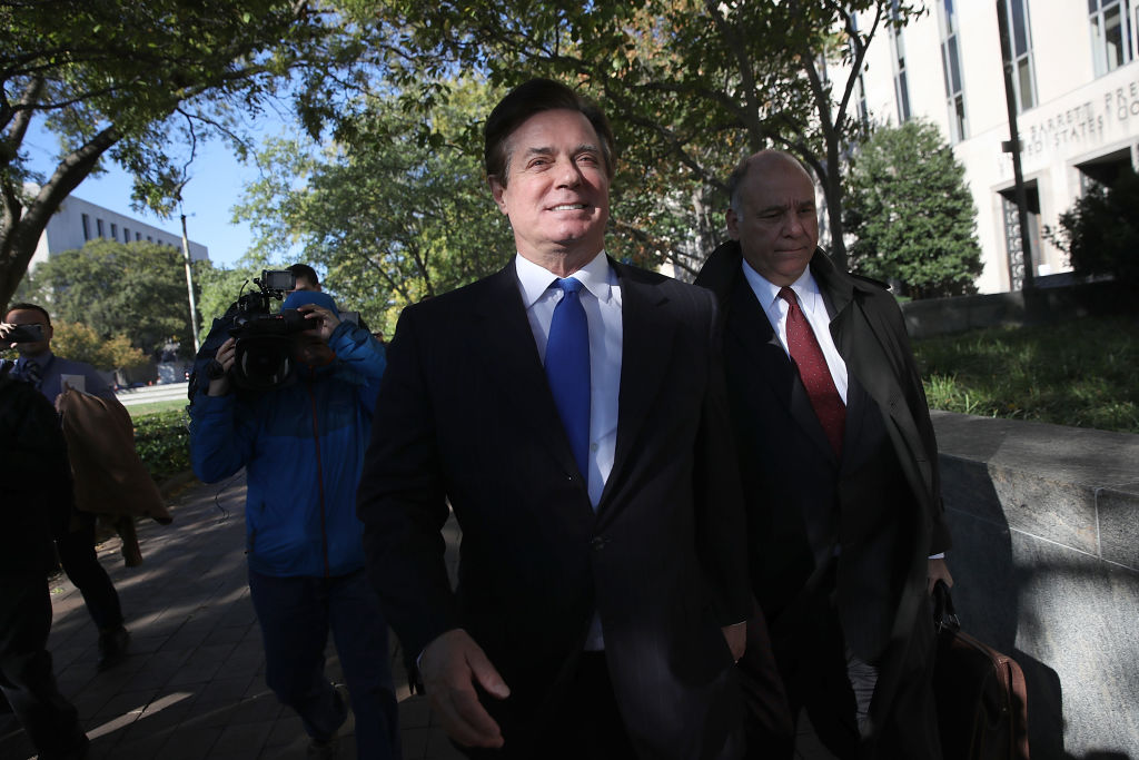 paul manafort in a dark suit and blue tie leaves his indictment