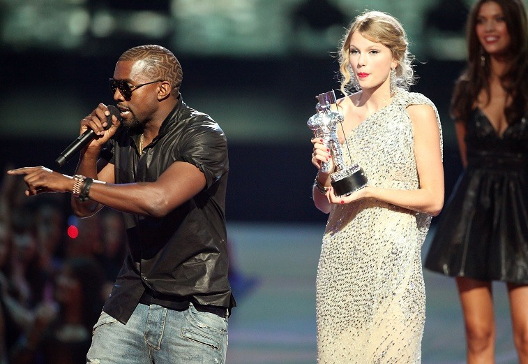 """Kanye West (L) jumps onstage after Taylor Swift (C) won the """"Best Female Video"""" award during the 2009 MTV Video Music Awards at Radio City Music Hall on September 13, 2009 in New York City"""