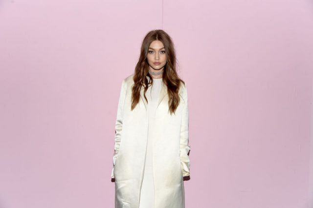 Gigi Hadid poses for photos in front of a pink background.