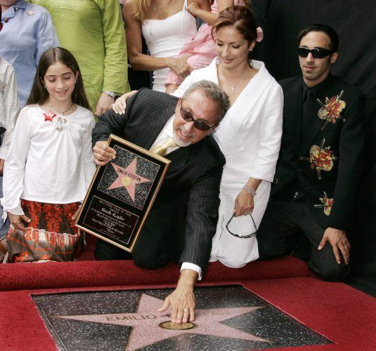 Emilio Estefan and his family pose in front of his star.