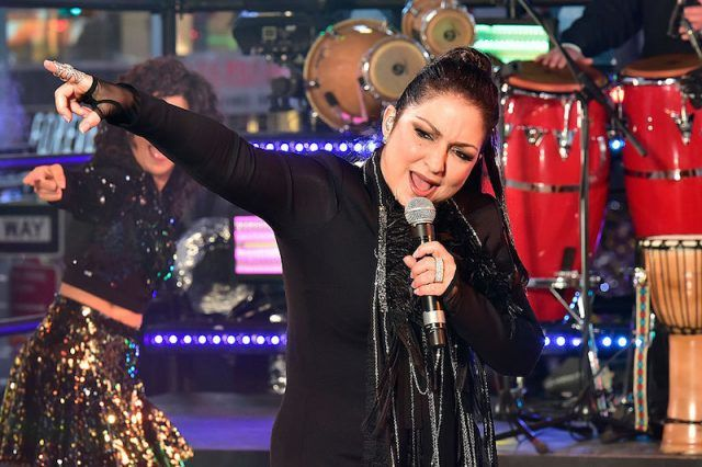 Gloria Estefan holding a microphone while performing on stage.