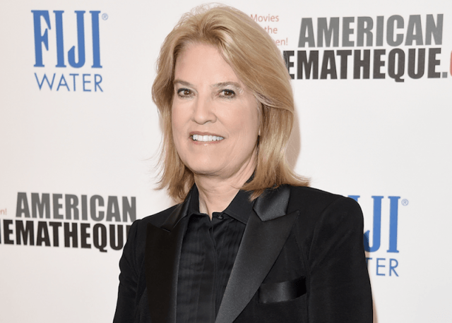 Greta Van Susteren standing in a black tuxedo on a red carpet.
