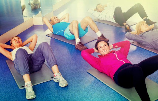 A group of people do crunches on mats.