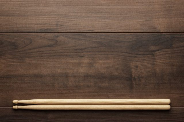 A pair of drumsticks on a wooden table.