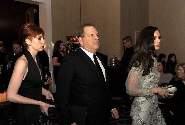 Harvey Weinstein stands in between two women