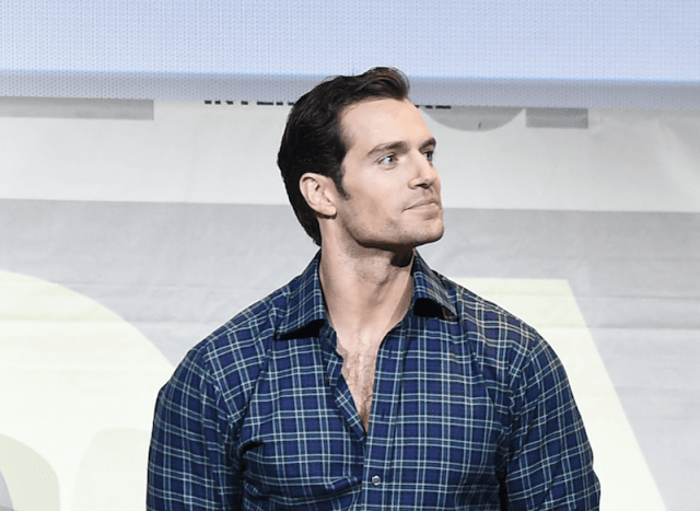 Henry Cavill wearing a plaid shirt and looking upwards to the left.