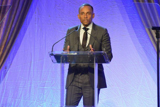 Hill Harper standing in front of a podium.