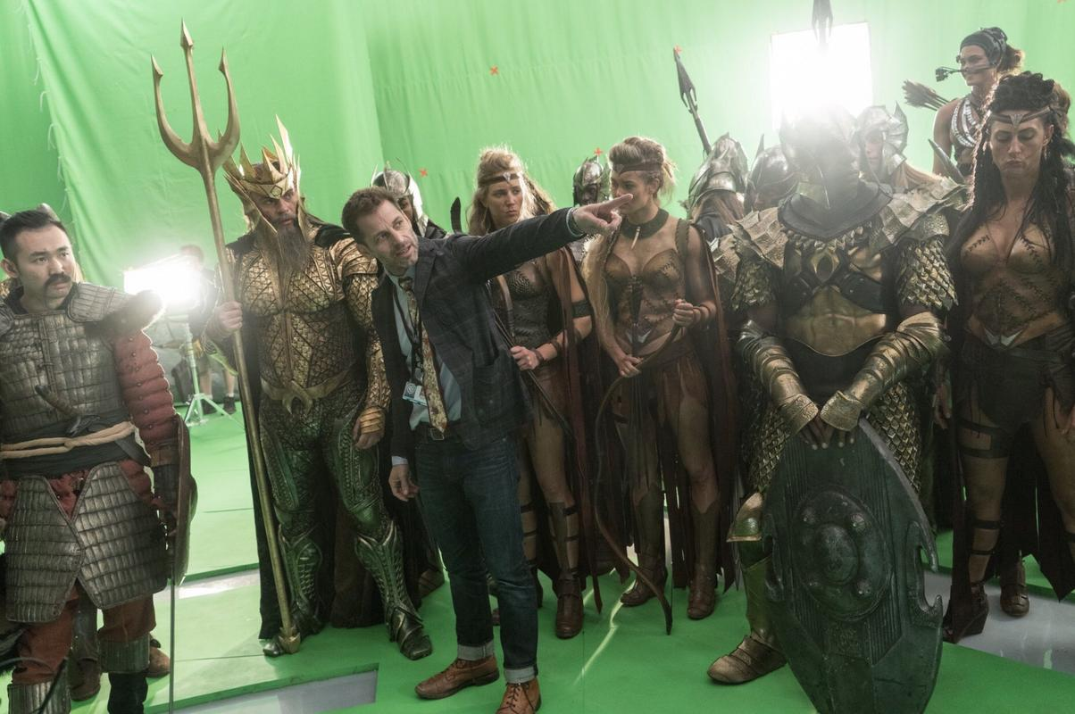 Zack Snyder points to something off=screen while standing in front of a group of actors on a green screen