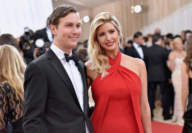Jared Kushner and wife Ivanka Trump stand together on a red carpet.