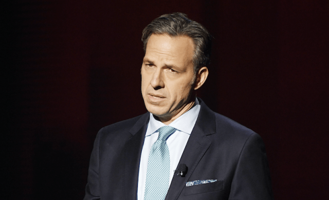Jake Tapper stands in a dark suit and light blue tie behind a dark curtain.