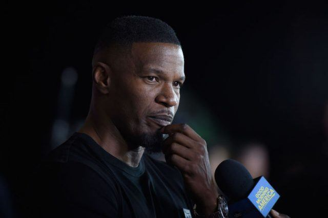Jaime Foxx standing in front of a microphone while holding his chin.