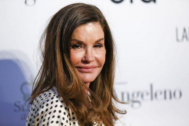 Janice Dickinson standing in a black and white polka dotted top while posing for photos at a fashion event.