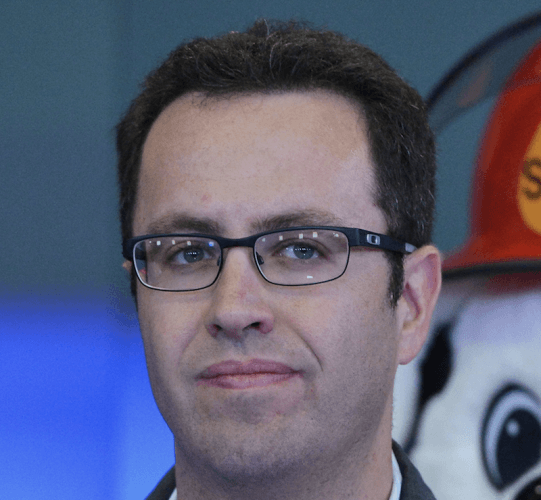 Jared Fogle wearing glasses and a suit at an event as he stares straight ahead.
